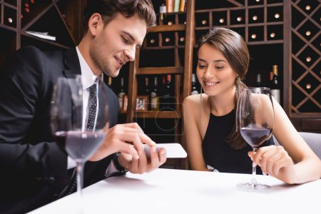 Selective focus of man in suit showing smartphone to girlfriend with glass of wine in restaurant