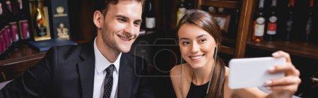 Photo pour Récolte panoramique de couple élégant prenant selfie sur smartphone dans le restaurant - image libre de droit
