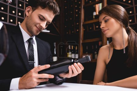 Photo for Selective focus of man in suit holding bottle of wine near elegant girlfriend in restaurant - Royalty Free Image