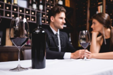 Photo for Selective focus of bottle and glass of wine on table near young couple holding hands in restaurant - Royalty Free Image