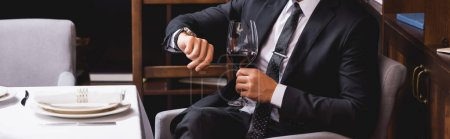 Website header of man in suit holding glass of wine and checking time in restaurant
