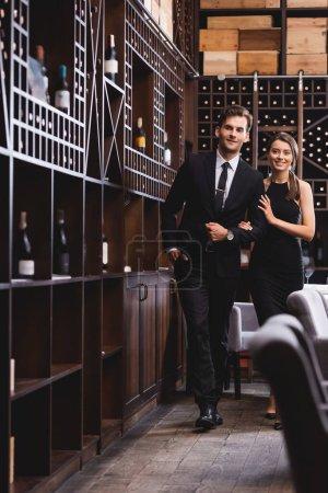 Photo pour Foyer sélectif de couple élégant marchant près des racks avec des bouteilles de vin dans le restaurant - image libre de droit