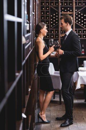 Selektiver Fokus eines Mannes im Anzug mit einem Glas Wein beim Dating mit einer eleganten Freundin im Restaurant