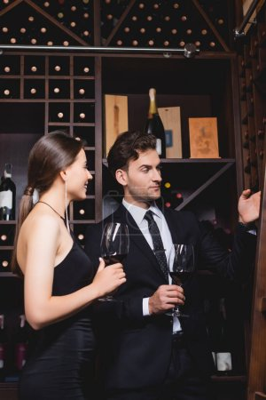 Photo for Man in suit pointing with hand at rack with bottles near elegant woman with glass of wine in restaurant - Royalty Free Image