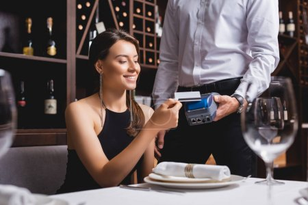 Selective focus of elegant woman holding credit card near waiter with payment terminal in restaurant