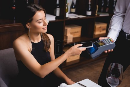 Selective focus of young elegant woman paying with cellphone near waiter with payment terminal in restaurant