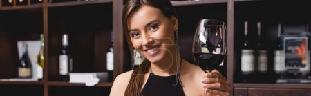 Photo for Panoramic shot of young woman holding glass of wine and looking at camera in restaurant - Royalty Free Image