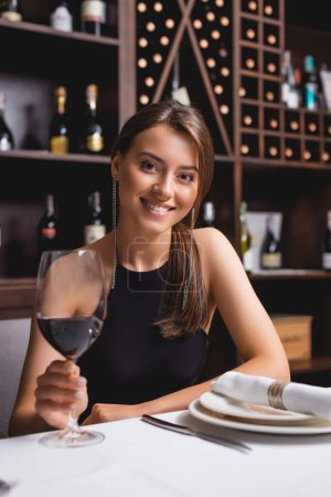Selective focus of young woman with glass of wine looking at camera n restaurant