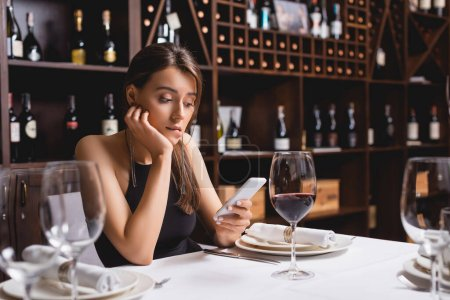 Selective focus of young woman using smartphone while sitting near glass of wine in restaurant