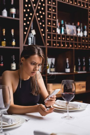 Selective focus of confused woman using smartphone while sitting near glass of wine in restaurant