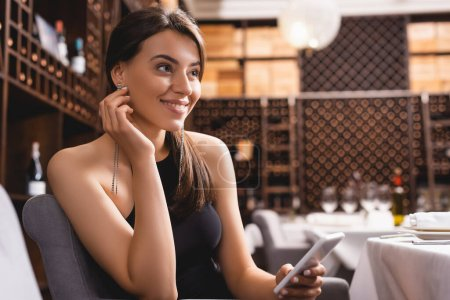 Photo for Selective focus of elegant woman looking away while holding smartphone in restaurant - Royalty Free Image