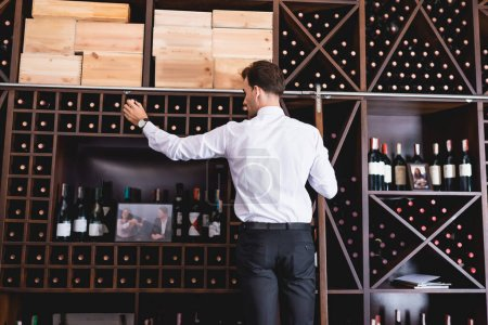 Photo for Back view of sommelier in formal wear taking bottle of wine from rack in restaurant - Royalty Free Image