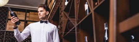 Photo for Panoramic shot of young sommelier looking at bottle of wine in restaurant - Royalty Free Image