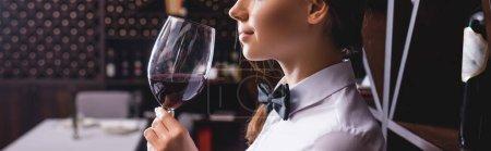 Panoramic shot of sommelier holding glass of wine in restaurant