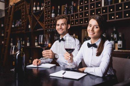 Photo pour Concentration sélective des sommeliers avec des verres de vin regardant la caméra dans le restaurant - image libre de droit