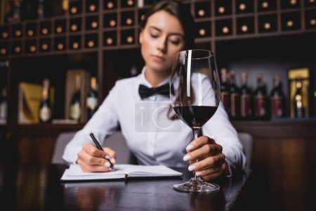 Selective focus of sommelier holding glass of wine while writing on notebook at table