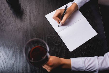 Cropped view of sommelier writing on notebook while holding glass of wine at table