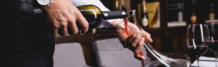 Panoramic shot of sommelier pouring wine in decanter near glasses in restaurant