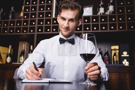 Photo pour Concentration sélective du sommelier regardant la caméra tout en tenant un verre de vin et en écrivant sur un carnet dans un restaurant - image libre de droit