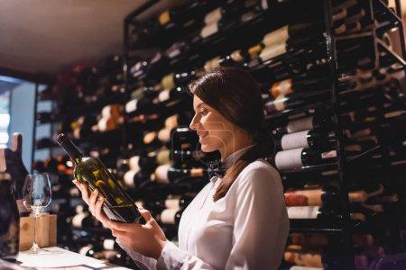 Selective focus of sommelier holding bottle of wine in restaurant