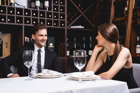 Selective focus of young couple looking at each other during dating in restaurant