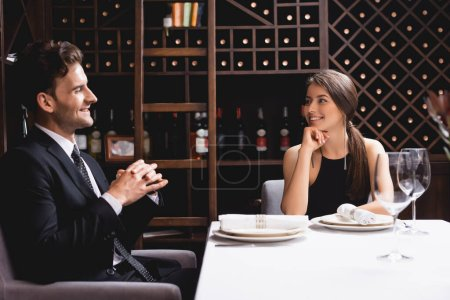 Selective focus of elegant couple looking at each other in restaurant