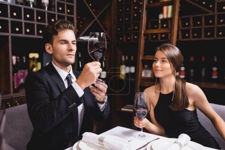 Photo pour Jeune homme en costume regardant un verre de vin près de petite amie dans le restaurant - image libre de droit