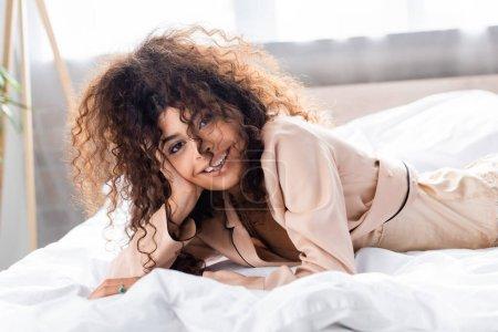 fröhliche und lockige Frau, die im Bett in die Kamera blickt