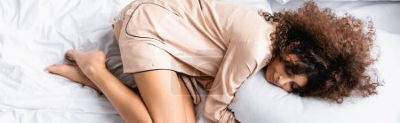 top view of curly woman with closed eyes hugging pillow while sleeping on bed, panoramic concept