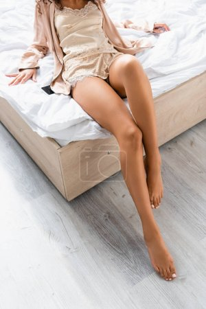 Photo pour Vue recadrée de la femme pieds nus assise sur le lit près du smartphone avec écran vierge - image libre de droit