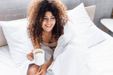 joyful woman laughing and holding cup of coffee