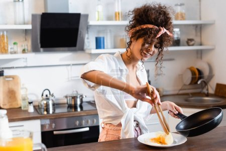 Photo for Curly and joyful woman holding frying pan and kitchen tongs while serving fried eggs on plate - Royalty Free Image