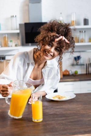 Photo pour Joyeuse femme tenant cruche près de verre et petit déjeuner sur assiette - image libre de droit