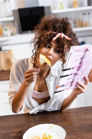 Photo for Curly woman eating delicious fried eggs and reading magazine - Royalty Free Image