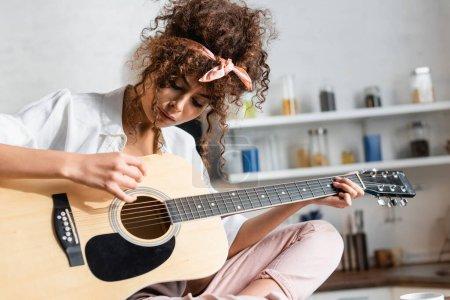 Photo pour Jeune femme bouclée jouant de la guitare acoustique à la maison - image libre de droit