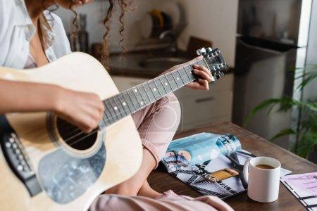 Photo pour Vue recadrée de jeune femme jouant de la guitare acoustique à la maison - image libre de droit