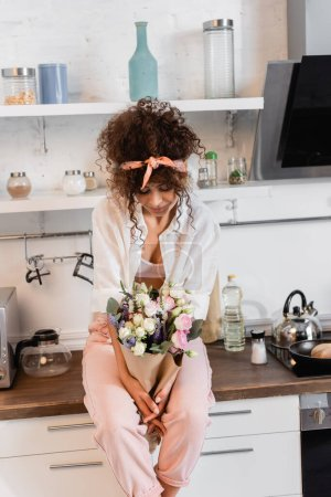 Photo for Curly woman sitting on kitchen table and looking at flowers - Royalty Free Image