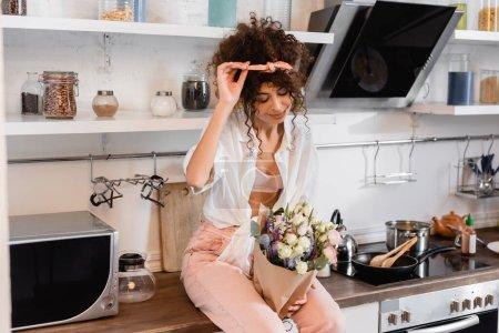 Photo pour Jeune femme bouclée assise sur la table de cuisine et regardant les fleurs - image libre de droit