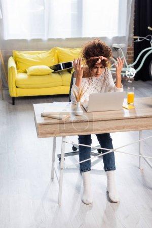 Photo pour Geste freelance mécontent tout en regardant ordinateur portable près des livres et un verre de jus d'orange sur la table - image libre de droit