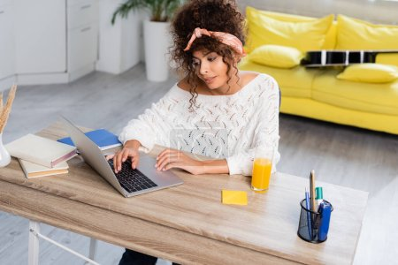 Photo for Curly freelancer looking at laptop near books and glass of orange juice on table - Royalty Free Image