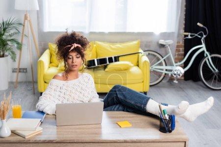 Photo pour Jeune freelance bouclé regardant ordinateur portable près des livres et un verre de jus d'orange sur la table - image libre de droit