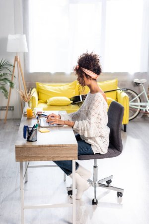 Photo for Side view of focused freelancer using laptop while working from hone - Royalty Free Image