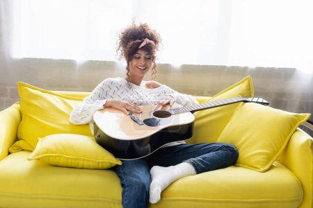 pleased woman holding acoustic guitar and sitting on sofa in living room