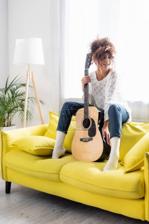 Frau mit Akustikgitarre auf gelbem Sofa im Wohnzimmer