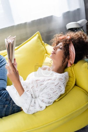 Photo for Pleased young woman reading book while lying on sofa in living room - Royalty Free Image