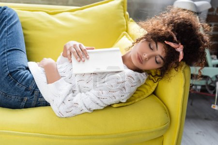 curly young woman sleeping with book in living room