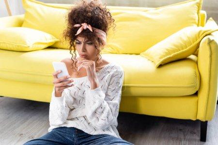 Besorgte Frau blickt neben gelbem Sofa auf Smartphone