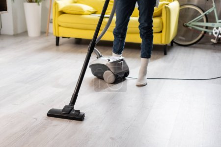 cropped view of woman in socks using vacuum cleaner while cleaning home