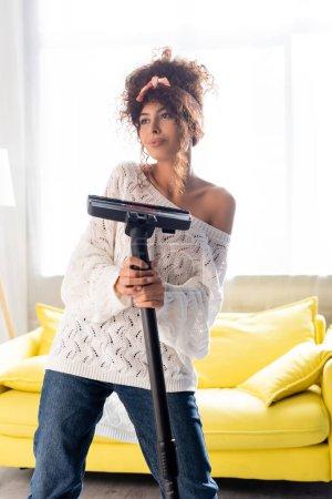Foto de Mujer joven sosteniendo la aspiradora y mirando hacia otro lado - Imagen libre de derechos