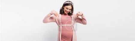 Photo pour Concept horizontal de femme enceinte joyeuse pointant avec les doigts vers le ventre sur blanc - image libre de droit